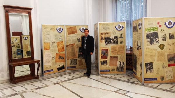 Prezes Zarządu Głównego Towarzystwa Opieki nad Zwierzętami w Polsce - Pan Łukasz Balcer na tle wystawy.