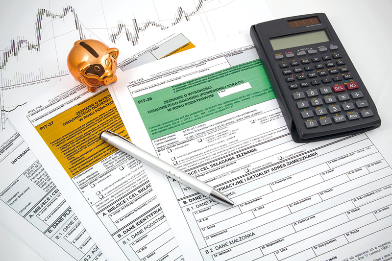 Polish income tax forms with calculator and piggybank